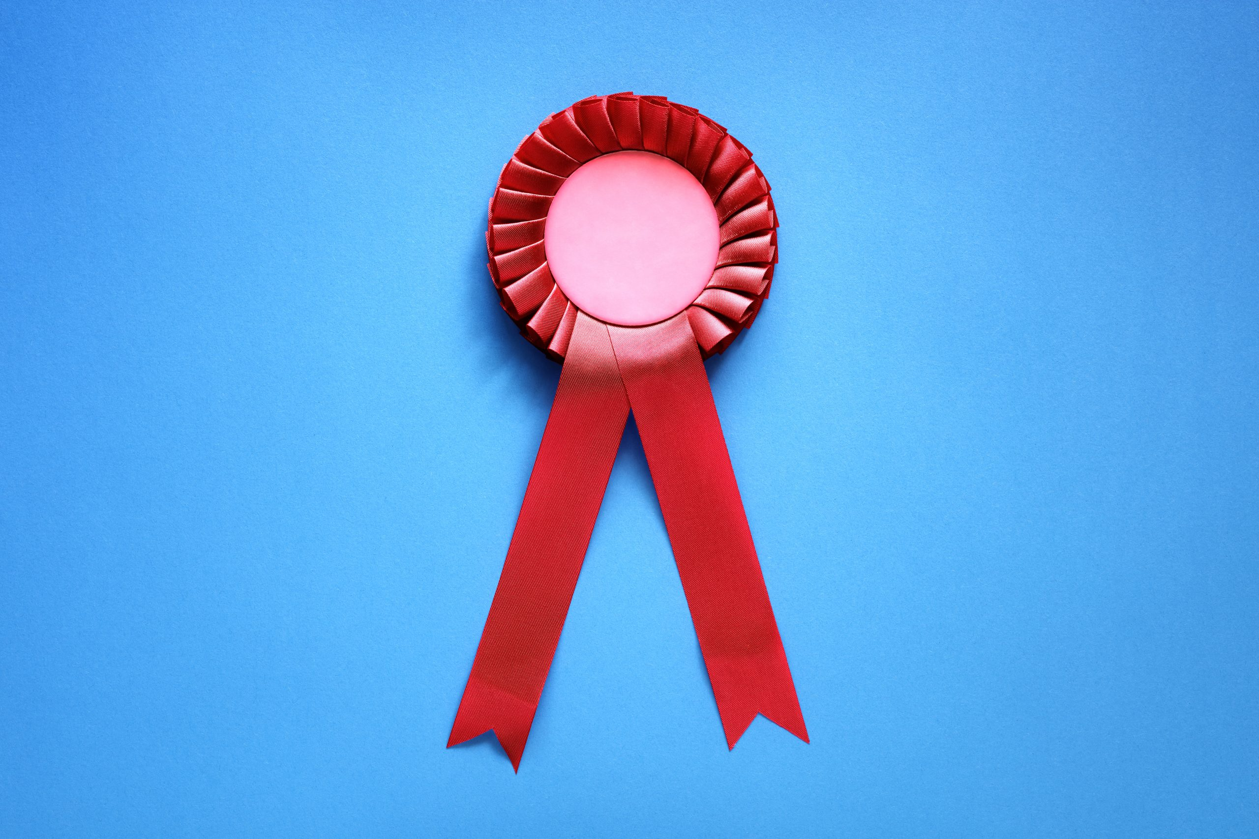 Red textile award rosette with ribbons